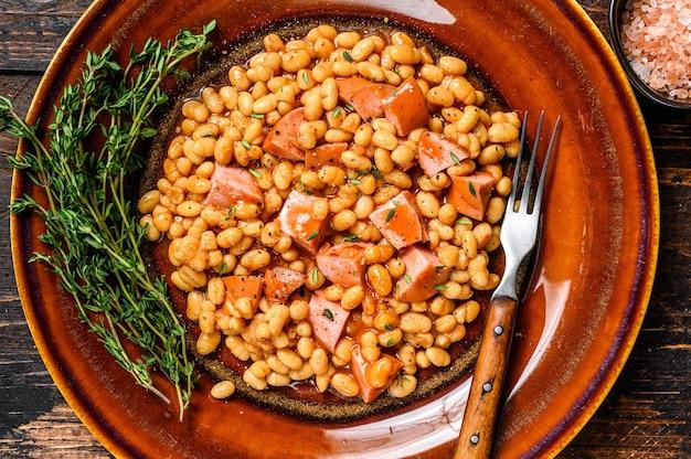 접시에 훈제 소시지와 토마토 소스를 곁들인 강낭콩. 어두운 나무 테이블. 평면도.