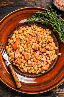 皿にスモークソーセージとトマトソースを添えたインゲン豆
