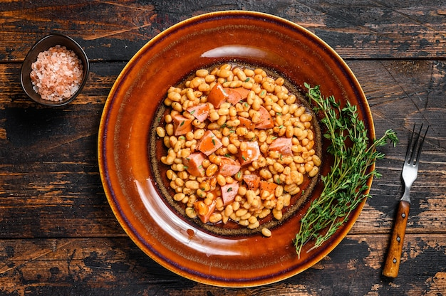 Kidney beans with smoked sausage and tomato sauce in a plate. dark wooden background. top view.