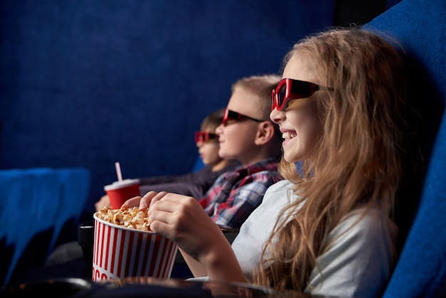 Kids in 3d glasses smiling, watching movie in cinema.
