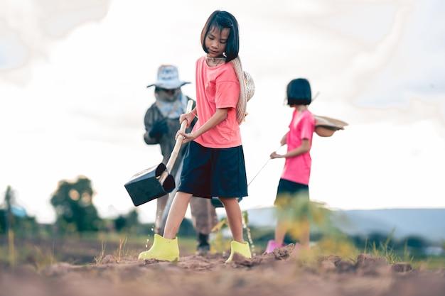 시골의 유기농 농장에서 일하고 야채에 물을 주는 아이들과 흐릿한 할머니