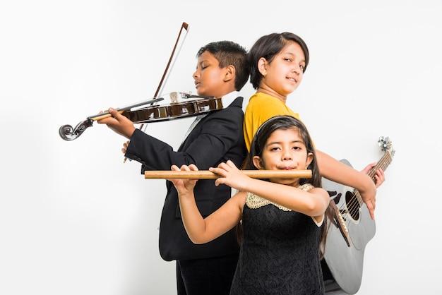 子供と音楽のコンセプト-白い背景の上に、チームまたはバンドとして楽器を演奏するかわいい小さなインドの子供たち