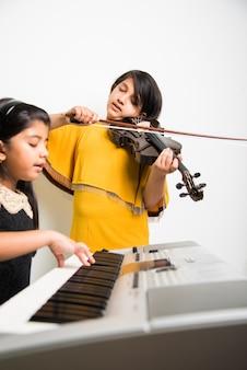 어린이와 음악 개념 - 피아노나 키보드, 바이올린 같은 악기를 연주하는 인도 소녀들