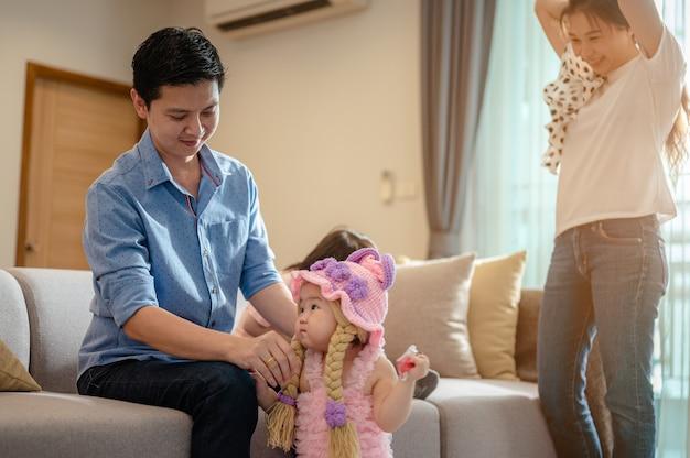 子供と親の幸せな家族全員がリビングルームのレジャー活動でソファに座って楽しんでいます