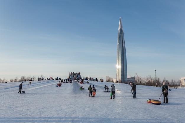 市街地の氷の斜面で子供と親がそり滑ります。