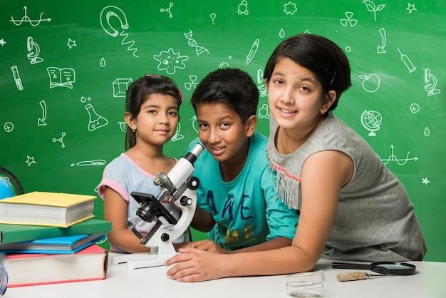 어린이와 과학 개념 - 귀여운 인도 꼬마 학생 또는 과학자가 과학을 공부하거나 현미경으로 실험하고 녹색 칠판에 도표 낙서를 하는 화학 물질을 실험합니다.