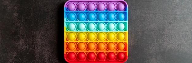 Детский антистрессовый сенсорный pop it или простая игрушка с ямочкой fidget push на черном столе или поверхности пола