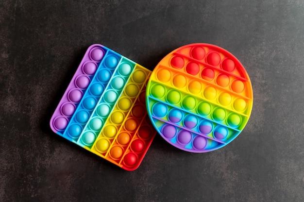 Детские антистрессовые сенсорные игрушки или простые игрушки-непоседы с ямочками на черном столе или поверхности пола