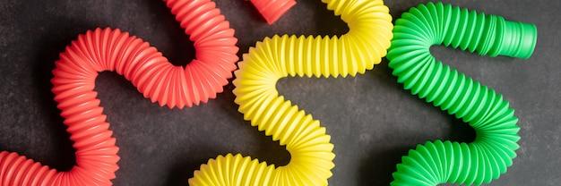 어린이 안티 스트레스 감각 팝 튜브 플라스틱 피젯 푸시 장난감은 검은색 테이블이나 바닥 배경에 있습니다. 어린이 작은 poptube 장난감 여러 가지 빛깔의 색조 밝은 색상. 배너. 평면도, 평면도