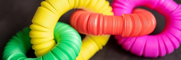 어린이 안티 스트레스 감각 팝 튜브 플라스틱 피젯 푸시 장난감은 검은색 테이블이나 바닥 배경에 있습니다. 어린이 작은 poptube 장난감 여러 가지 빛깔의 색조 밝은 색상, 트렌드 2021 년. 배너