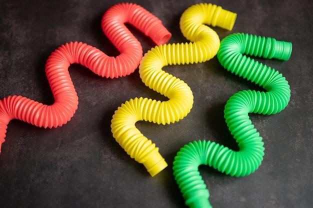 어린이 안티 스트레스 감각 팝 튜브 플라스틱 피젯 푸시 장난감은 검은색 테이블이나 바닥 배경에 있습니다. 어린이 작은 poptube 장난감 여러 가지 빛깔의 색조 밝은 색상, 트렌드 2021 년. 평면도, 평면도