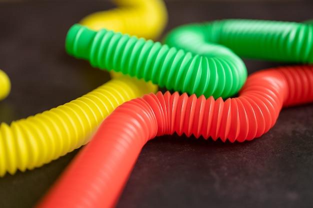 어린이 안티 스트레스 감각 팝 튜브 플라스틱 피젯 푸시 장난감은 검은색 테이블이나 바닥 배경에 있습니다. 어린이 작은 poptube 장난감 여러 가지 빛깔의 색조 밝은 색상, 동향 2021 년