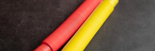 어린이 안티 스트레스 감각 팝 튜브 플라스틱 피젯 푸시 장난감은 검은색 테이블이나 바닥 배경에 있습니다. 어린이 작은 팝튜브 장난감 빨간색과 노란색 색조 밝은 색상. 배너. 평면도, 평면도