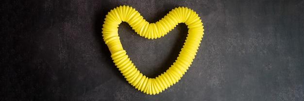 어린이 안티 스트레스 감각 팝 튜브 플라스틱 피젯 푸시 장난감은 검은색 테이블이나 바닥 배경에 있습니다. 어린이 작은 팝 튜브 장난감 노란색 색조 밝은 색상. 배너. 평면도, 평면도