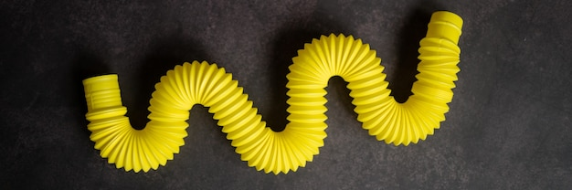 子供の抗ストレス感覚ポップチューブプラスチックそわそわは、黒いテーブルや床の背景におもちゃを押します。子供の小さなポップチューブのおもちゃ黄色の色合いの明るい色。バナー。上面図、フラットレイ