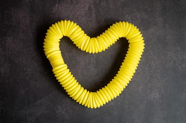어린이 안티 스트레스 감각 팝 튜브 플라스틱 피젯 푸시 장난감은 검은색 테이블이나 바닥 배경에 있습니다. 어린이 작은 poptube 장난감 노란색 색조 밝은 색상, 트렌드 2021 년. 평면도, 평면도