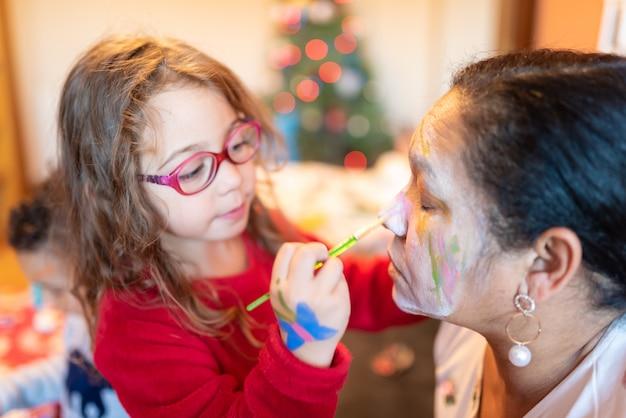 Kids applying make up to grandmother.