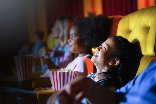 Kids are seating and watching a movie at cinema