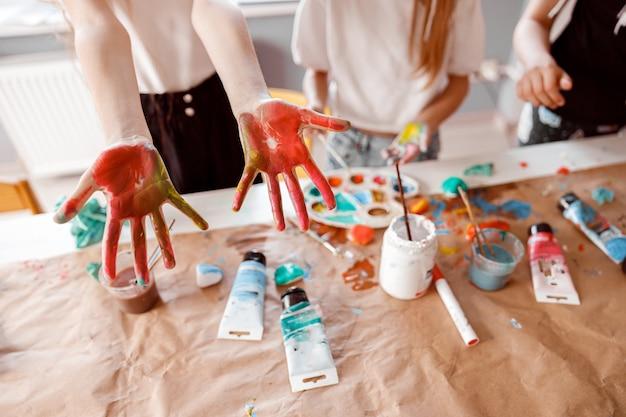 子供たちは水彩で描かれた手のひらを見せています