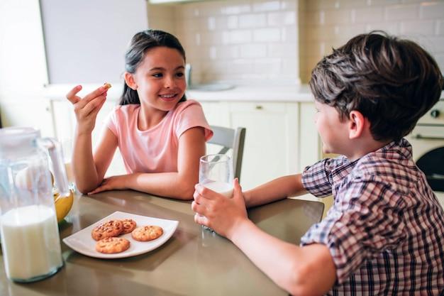 아이들이 테이블에 앉아 있습니다. 그녀는 쿠키를 먹고있다. 소년 우유 컵을 보유하고있다. 그들은 서로를보고 웃고 있습니다. 아이들은 혼자입니다.