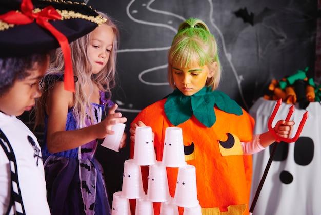 플라스틱 컵의 피라미드를 배열하는 아이들