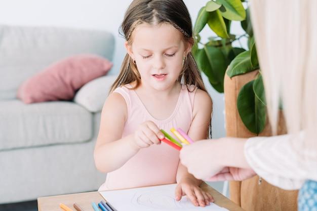 Детский творческий досуг. живопись искусство хобби. маленькая девочка и ее мама рисуют рисунки карандашами.