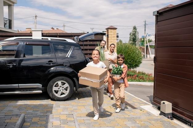 両親が車を降ろすのを手伝う子供たち
