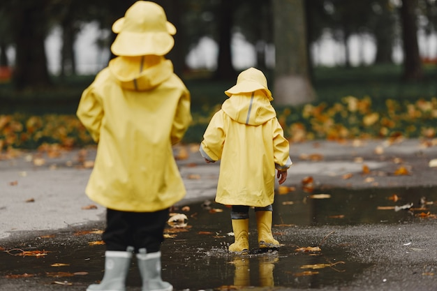 Kids in a autumn park. children in a yellow raincoats. people having fun outdoors.