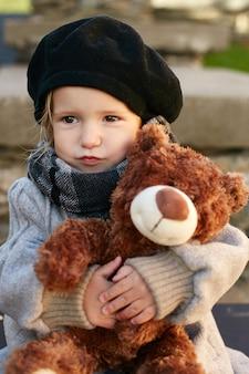 복고풍 가을 봄 옷에 아이 아기. 자연 속에서 웃고 앉아있는 작은 아이, 목에 스카프