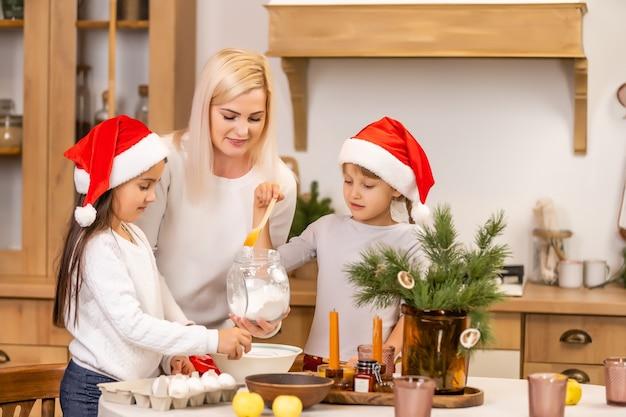 クリスマスのお祝いの前にクリスマスクッキーを焼く子供たち。家族