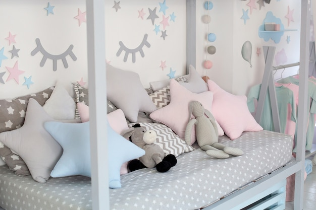 Kids bed in white sunny bedroom. children room and interior design. bed for baby or toddler at home. bedding and textile for children nursery. nap and sleep time. children bedroom with pillows.