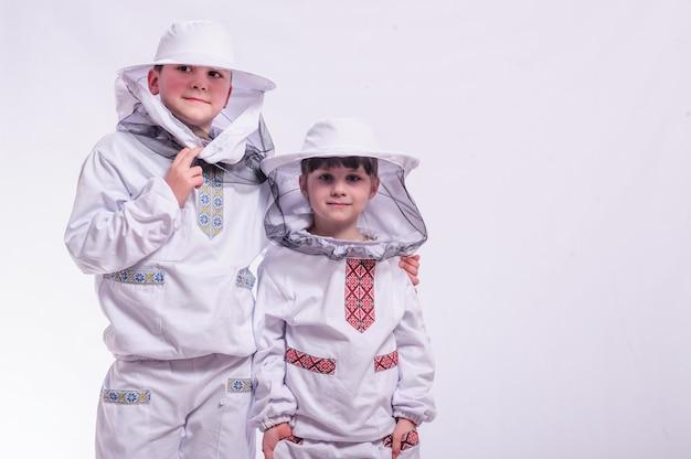 Kids in beekeeper's suits posing in studio white background.
