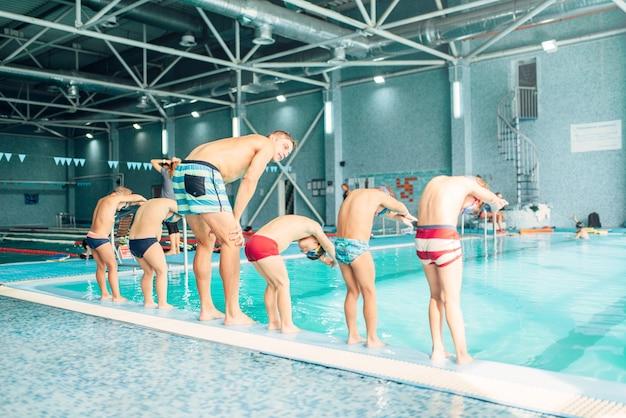 아이들은 몸을 구부리고 수영장에 뛰어들 준비를합니다.