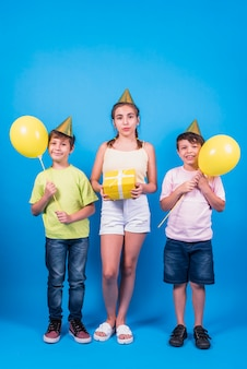 Kids in birthday hat holding yellow gift and yellow balloons against blue backdrop