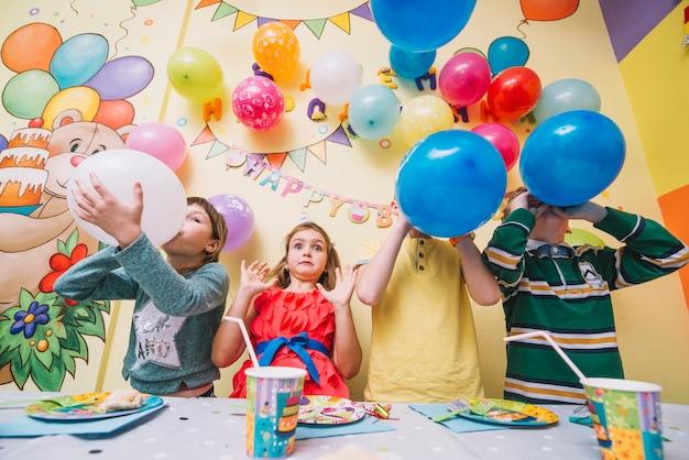 I bambini che soffia palloncini durante la festa di compleanno