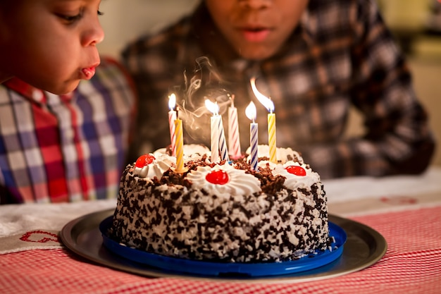 ケーキを吹く子供たちがろうそくを吹き消す黒人の男の子がろうそくを吹き消す謙虚な誕生日パーティーを食べる時間はありません