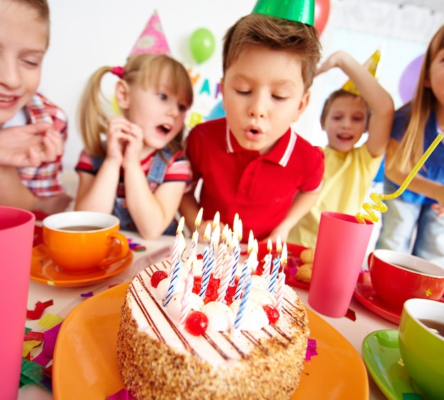 Kids blowing candles on birthday party