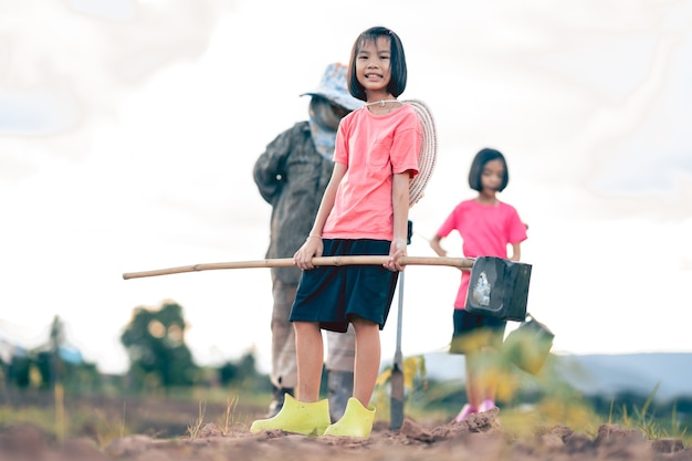 Kids and blurred grandmother working and watering the vegetable in organic farm in rural