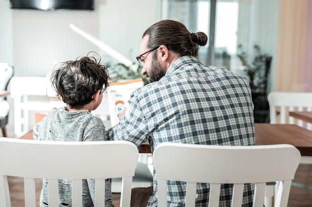 キッズブック。レストランで注文を待っている間に子供向けの本を読んでいる父と息子