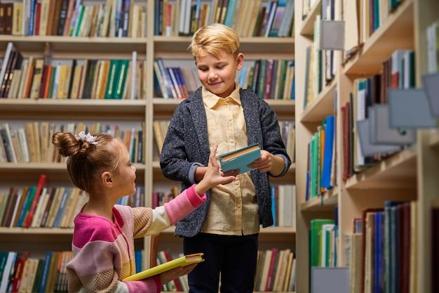 어린이 소년과 소녀는 학교 도서관에서 책을 선택하고 읽고 지식을 얻습니다.