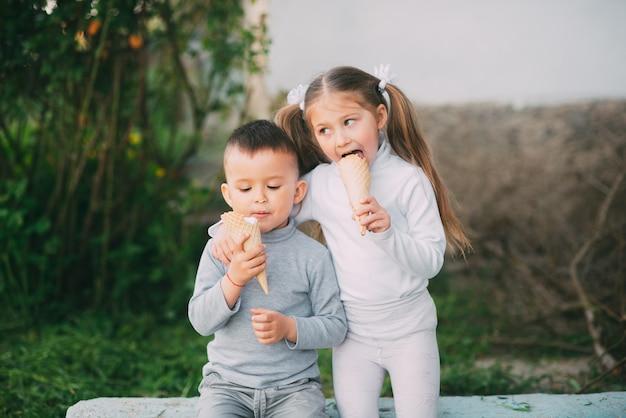 子供の男の子と女の子の屋外の草や木の背景にアイスクリームを食べるとても甘い