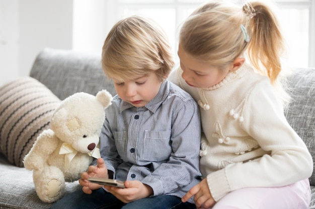 Kids boy and girl using smartphone together sitting on sofa