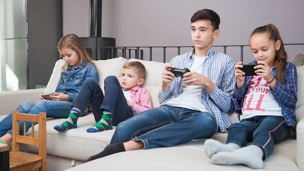 Kids browsing smartphones near teenager with controller
