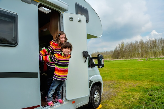 Kids in camper, family travel in motorhome on vacation