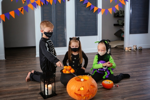 Kids in carnival costumes are celebrating halloween wearing face masks and playing with pumpkins