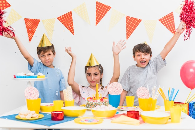 Kids celebrating birthday party at home with variety of food on table