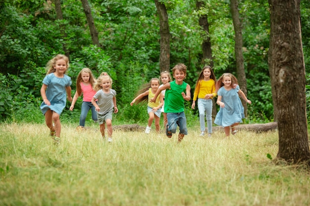 Kids, children running on green meadow