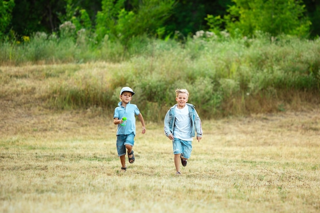 Kids, children running on meadow in summer's sunlight. look happy, cheerful with sincere bright emotions. cute caucasian boys and girls.
