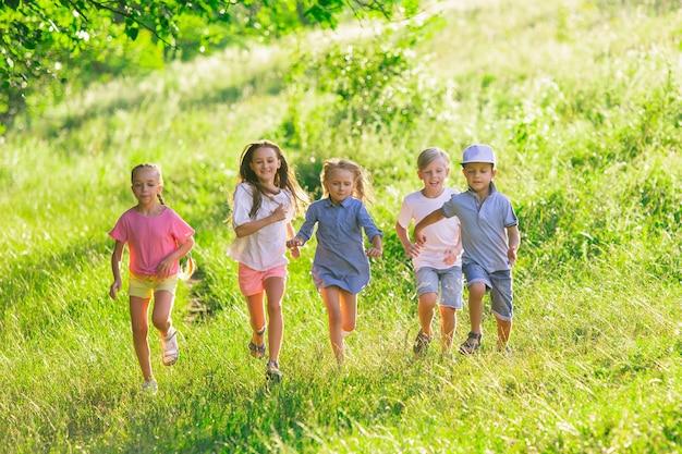 Kids, children running on meadow in summer's sunlight.