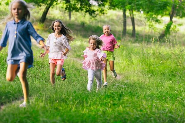 Kids, children running on meadow.